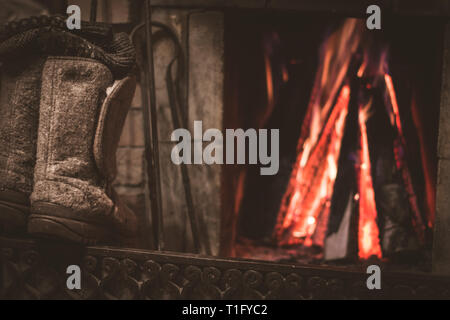 Old felt boots and fireplace with warm fire on the background - Stock Photo