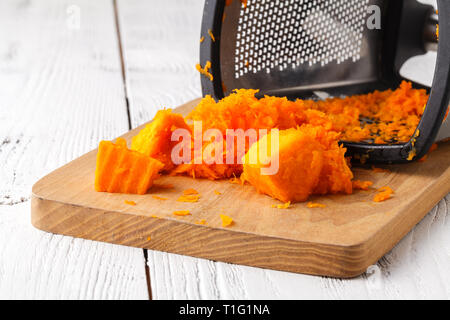 Sliced and chopped pumpkin pieces. Pumpkin chunks on wooden background. Fresh and ripe pumpkin detail vegetable and halloween composition - Stock Photo