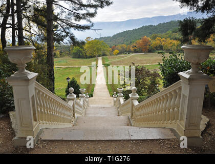 A white stone staircase in the autumn garden leads to the yellow autumn trees on a background of mountains with autumn clouds - Stock Photo