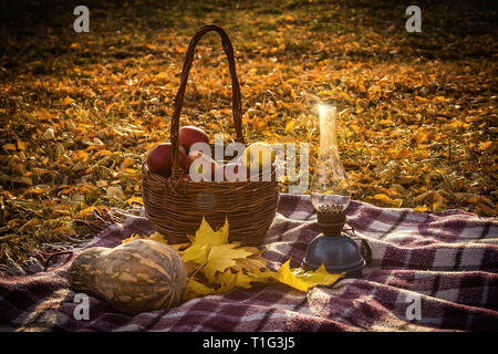 Autumn still life with red apples in a basket, pumpkins, leaves and oil lamp. - Stock Photo