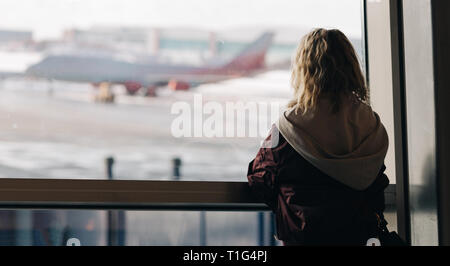 Photo from back of blonde near window with plane flying by in afternoon . - Stock Photo