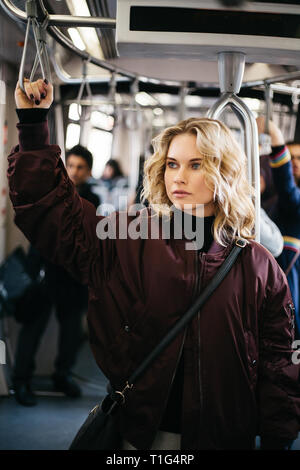 Photo of curly blonde woman riding in bus. - Stock Photo