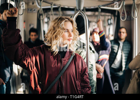Image of curly blonde riding in bus. - Stock Photo