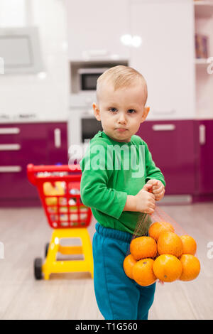 Little boy holds a grid with oranges. Little kid in casual wear carrying child plastic shopping trolley. Shopping, discount, sale concept - Stock Photo