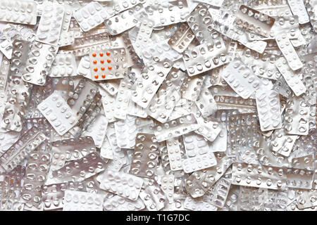 Orange pills in blister pack in front of many empty packages, drug overdose concept background - Stock Photo