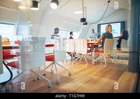 Manager discussing graphs on a monitor during a meeting with a diverse group of colleagues sitting around a table inside of a glass office - Stock Photo