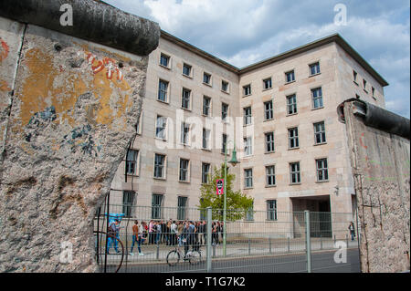 Berlin, Germany:: View to Niederkirchnerstraße through a damaged section of the original Berlin Wall. Today it is fenced to prevent further damage. - Stock Photo