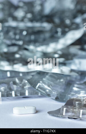 One single tablet in front of many empty blister packages on white background, drug misuse concept - Stock Photo
