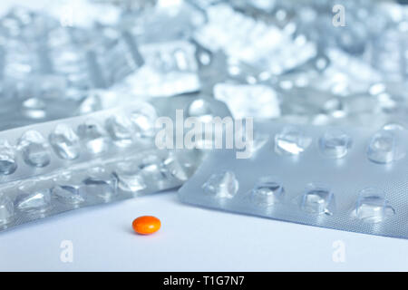 One single pill in front of many empty blister packages on white background, drug misuse concept - Stock Photo