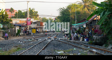 People living beside a railway line. Family life goes on beside a litter strewn railroad track near Battambang, Cambodia, train station. Dec 2018 - Stock Photo