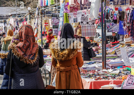 Open air street vendors selling clothes & other merchandise products at stalls every Saturday at a large weekly bazaar flea market in Xanthi, Greece. - Stock Photo