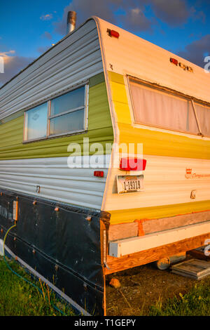 An old camper trailer seems to have seen better days and is now off the grid living at sunset in Montana, USA - Stock Photo