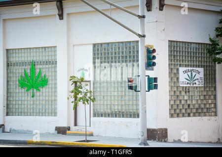 The exterior of Therapeutic Buds, a medical marijuana dispensary with a Marijuana leaf painted on ice brick window in Butte, MT, USA - Stock Photo