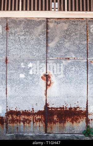 old detailed aged vintage rusty red brown textured zinc alloy metal sheet exterior fence door used in construction industry as warehouse building mate - Stock Photo