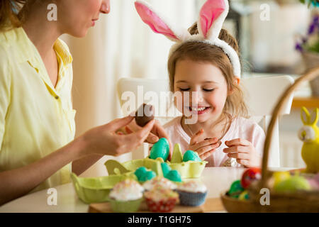 Mother and daughter celebrating Easter, eating chocolate eggs. Happy family holiday. Cute little girl with funny face in bunny ears laughing, smiling - Stock Photo