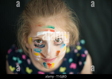 pretty little caucasian girl in multicolored dress with painted colorful face smiling - Stock Photo