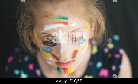 beautiful little girl in multicolored with eyes closed with painted colorful face dreaming - Stock Photo