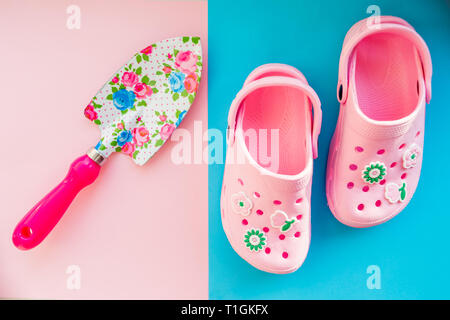 rubber boots and garden tools on bright background.kids summer sandals and shovel with flowers pattern.Kid's toys and boots for beach.Summer concept - Stock Photo
