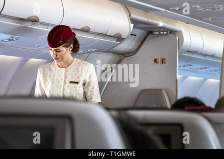 Doha, Qatar - February 20th, 2019: A female cabin crew flight attendant speaking with a passenger onboard on Airbus A350 of Qatar Airways.