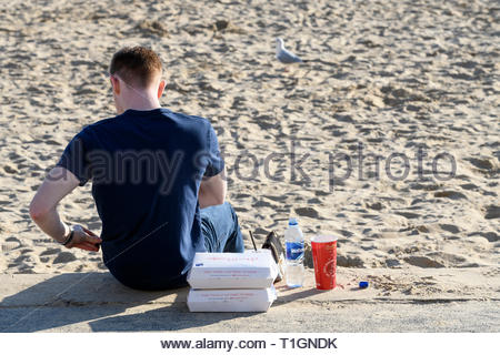 Man sitting on beach, Bournmouth, Dorset, England, UK - Stock Photo
