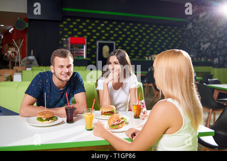 Happy company sitting at table in cafe and having rest together. Young boy and pretty girls eating tasty burgers and drinking juice while talking. Concept of relax and friendship. - Stock Photo