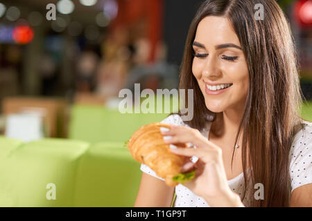 Cheerful young woman sitting in nice cafe and enjoying tasty snack. Beautiful brunette keeping delicious croissant with greens and ham and looking at it. Concept of eating yummy food. - Stock Photo