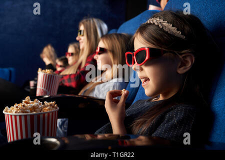 Children sitting in movie theatre, watching film or cartoon, wearing in 3d glasses. Cheerful little girl eating popcorn, holding popcorn bucket. - Stock Photo