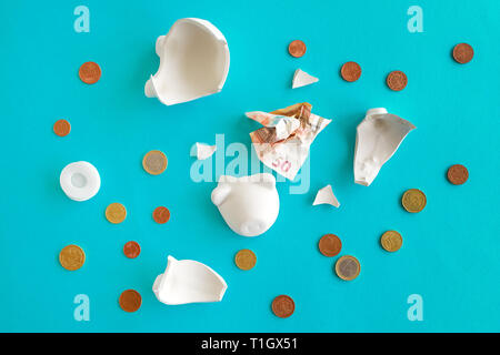 Euro coins and paper currency in broken piggy coin bank, money savings in home budget and finances concept - Stock Photo