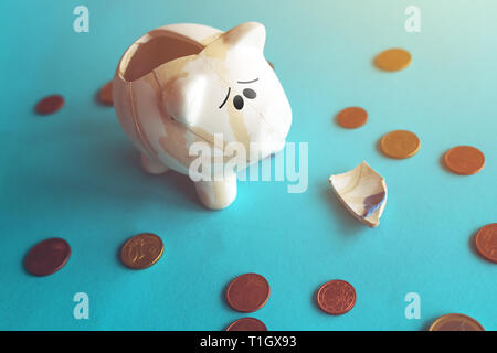 Euro coins in glued broken piggy coin bank, money savings in home budget and finances concept - Stock Photo