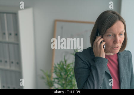 Businesswoman in mobile phone conversation by the office window, adult female caucasian business person talking on smartphone - Stock Photo