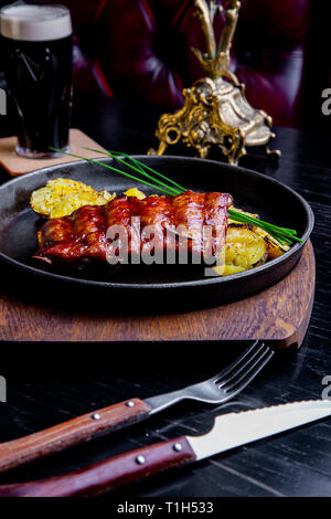 Close up Gourmet Main Dish with Grilled Pork Rib and Fried Potatoes on Black pan. Served on Wooden Board - Stock Photo