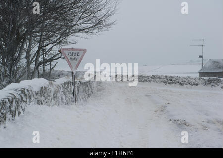 snow covered road junction in rural location, with give way warning sign covered in snow - Stock Photo