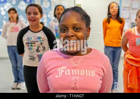 School children having fun during a dance class in a school hallway. - Stock Photo