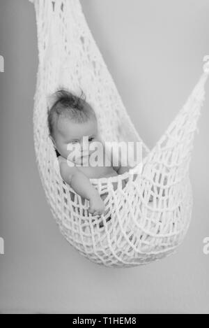 Newborn Baby relaxing in a white hammock with soft bright background - happy family moments - Stock Photo