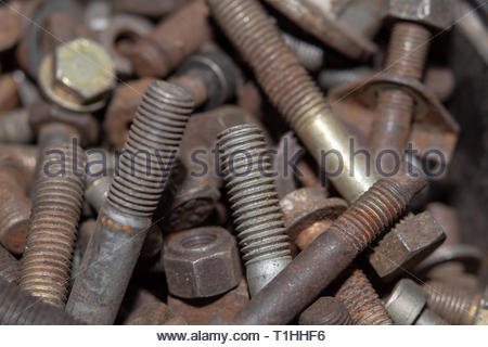 Pile of old rusty screw heads, bolts, metal nuts. Bolt used overlapping full. Bolts and screws used in constructions - Stock Photo