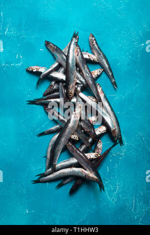 Seafood. Small sea fish, anchovies, sardines on the blue background. Fish pattern - Stock Photo