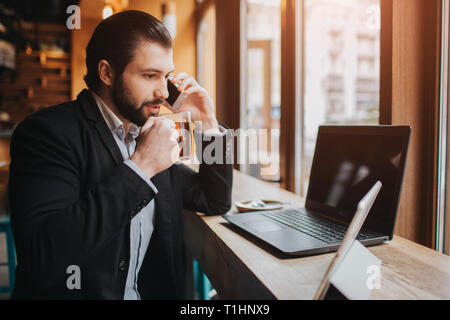 Busy man is in a hurry, he does not have time, he is going to eating and working. Worker eating, drinking coffee, talking on the phone, at the same - Stock Photo