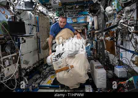 Canadian Space Agency astronaut David Saint-Jacques moves a U.S spacesuit inside the Destiny laboratory module March 19, 2019 in Earth Orbit. - Stock Photo