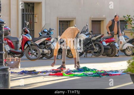 Seville, Spain - March 9, 2019: African immigrant selling their wares on the Constitution Avenue in Seville, Spain. This is a common practice in Spain - Stock Photo