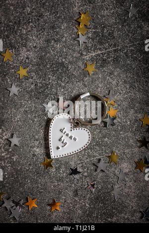 Keyring in the shape of heart and slogan DREAM BIG. Minimalist Concept of ambitions and reaching goals - Stock Photo