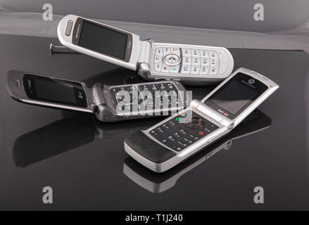 Old Classic Flip Style Cell Phones on Black - Stock Photo