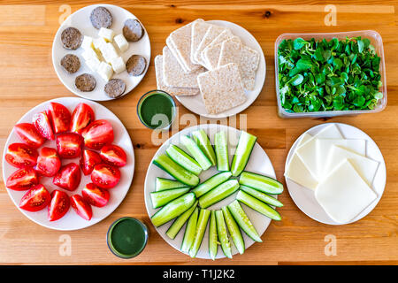 Wooden table with food flat top view setting of healthy vegan vegetarian lunch or dinner and green vegetable juice cheese slices salad cucumbers and t - Stock Photo