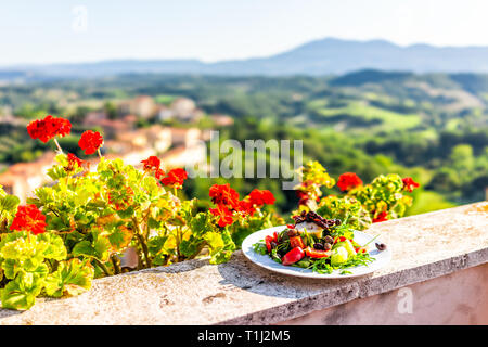Arugula salad with olives on plate on balcony terrace by red geranium flowers in garden outside in Italy in Tuscany mountain view - Stock Photo