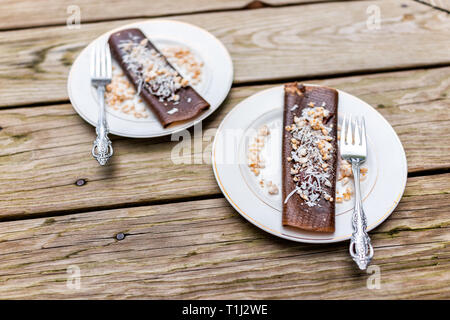 Closeup of two chocolate crepe dessert wraps with coconut flakes made in dehydrator with bananas on plates and forks - Stock Photo