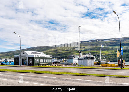 Akureyri, Iceland - June 17, 2018: Street view on large town fishing village with fjord and empty road with whale watching tour buildings - Stock Photo