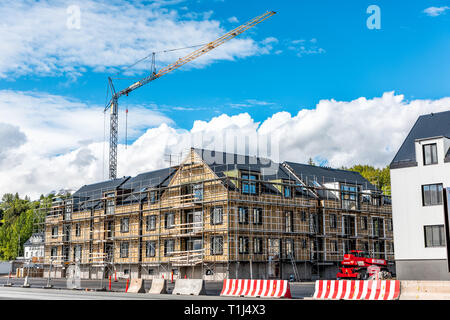 Akureyri, Iceland - June 17, 2018: Street view in large town fishing village by fjord and construction on building with crane and blue sky - Stock Photo