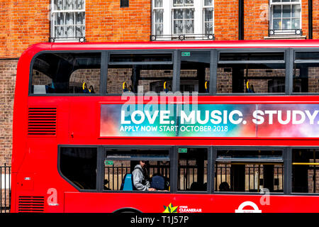 London, UK - June 21, 2018: Closeup of red double decker bus on street road win center of downtown city with advertisement sign for love music study - Stock Photo