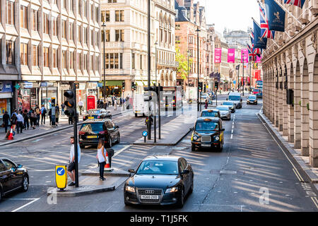 London, UK - June 22, 2018: High angle view of Piccadilly Circus Regent street with cars taxi cabs black on street traffic on road with banners hangin - Stock Photo