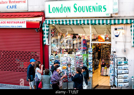 London, UK - June 22, 2018: Store vendor shop by street selling many souvenirs and sign with people tourist asian looking at postcards magnets on disp - Stock Photo