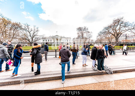 Washington DC, USA - March 9, 2018: Crowd of many people tourists at White House President building in capital city of United States in cold winter on - Stock Photo